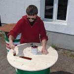 Daniel beim Lackieren der Holzplatte